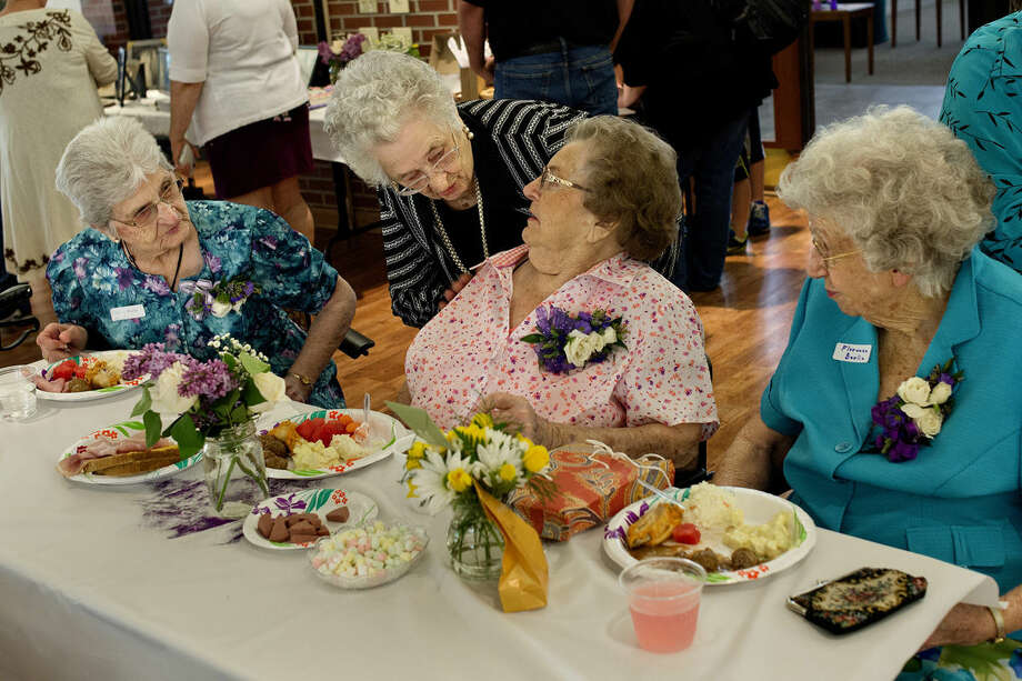 Edith Woods, center, leans over to speak with Alice Owens as Marie Berlin, left, and Florence Berlin, right, look on during Alice, Marie and Florence's 90th birthday party on Saturday at the Greater Midland Community Center. Photo: Nick King | Nking@mdn.net