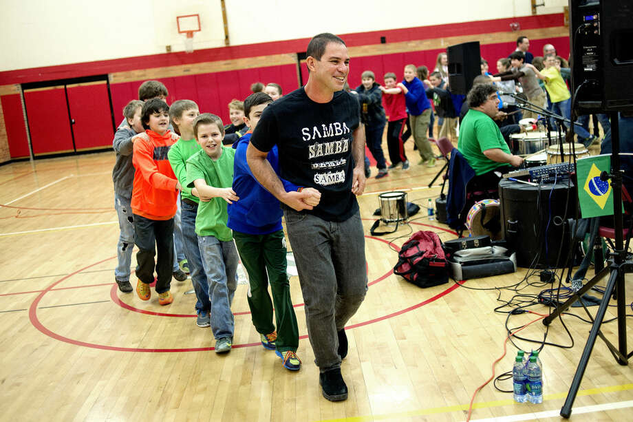 Brazilian musician Paulo Padilha leads a conga line with students around the gym as Padilha's group plays music on Monday at Jefferson Middle School. Padilha and his group will be performing at the Midland Center for the Arts on Friday night. Photo: NICK KING | Nking@mdn.net
