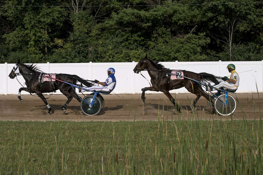 Darrell Wright and his horse You Know Hoo inch ahead of Larry Lee Smith and his horse Every Step Counts during the 2-year-old filly 1 mile trot during the Midland County Fair harness racing competition at the Midland County Fairgrounds in Midland on Tuesday. Wright came in second and Smith came in third. Photo: ERIN KIRKLAND | Ekirkland@mdn.net