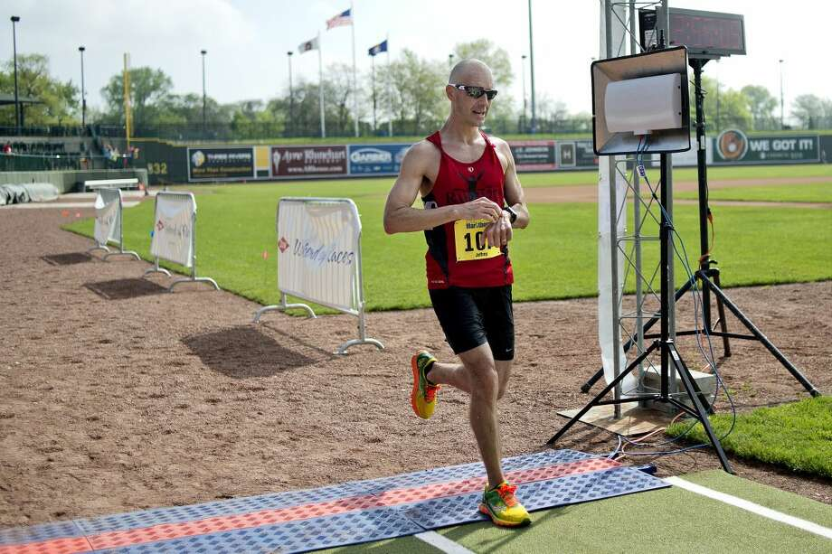 NICK KING l nking@mdn.net Jeffery Schlenker crosses the finish line as the overall winner in the marathon race during the Great Lakes Bay Marathons on Sunday at Dow Diamond. Photo: Nick King/Midland Daily News