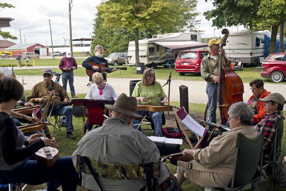 Festival goers play an assortment of instruments ranging from the cello to the mountain dulcimer on Thursday at the 2015 Midland Folk Music Festival at the county fairgrounds. The festival will continue throughout the weekend until Sunday at noon with workshops, performances, vendors and more. Photo: Erin Kirkland | Midland Daily News
