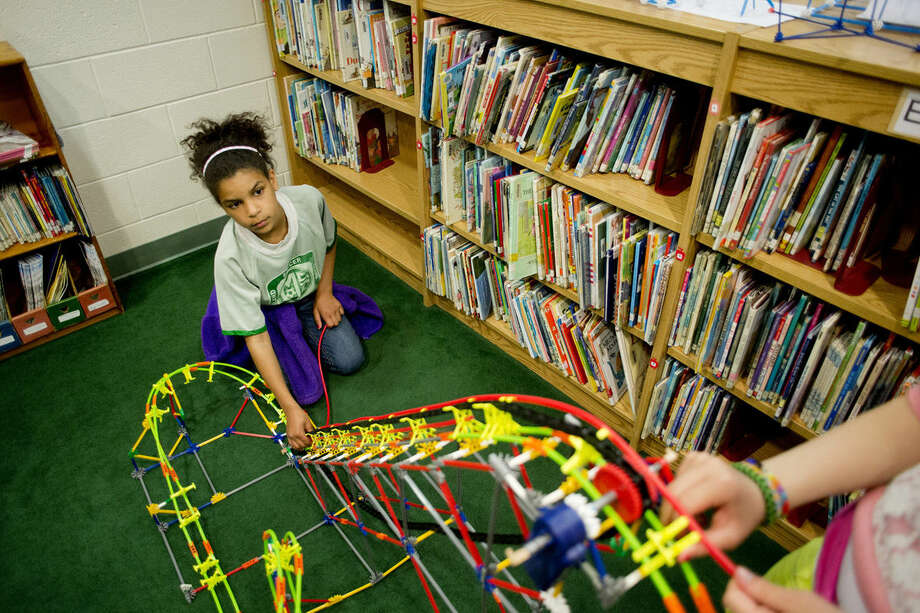 """Floyd Elementary School fifth-grader Nuru Ouda looks up at Alyssa Brown, also a fifth-grader, as they work on assembling a K'NEX roller coaster in the school library. The two students are part of an informal """"Building Club"""" and they use their lunch and recess to build things on Tuesdays and Fridays with K'NEX, Legos, Zometools, Elenco Snap Circuit Kits and Solar Robot Kits. Photo: Neil Blake 
