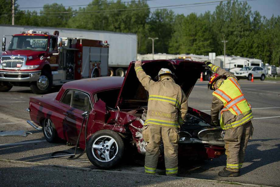 Firefighters look under the hood of a 1961 Pontiac Tempest as they disconnect the battery after a three-car accident at the intersection of M-20 and Meridian Road on Thursday morning. The Homer and Lee township fire departments responded to the scene with ambulances from MidMichigan Medical Center-Midland. At least one person was transported for injuries sustained during the crash. Photo: Neil Blake/Midland Daily News