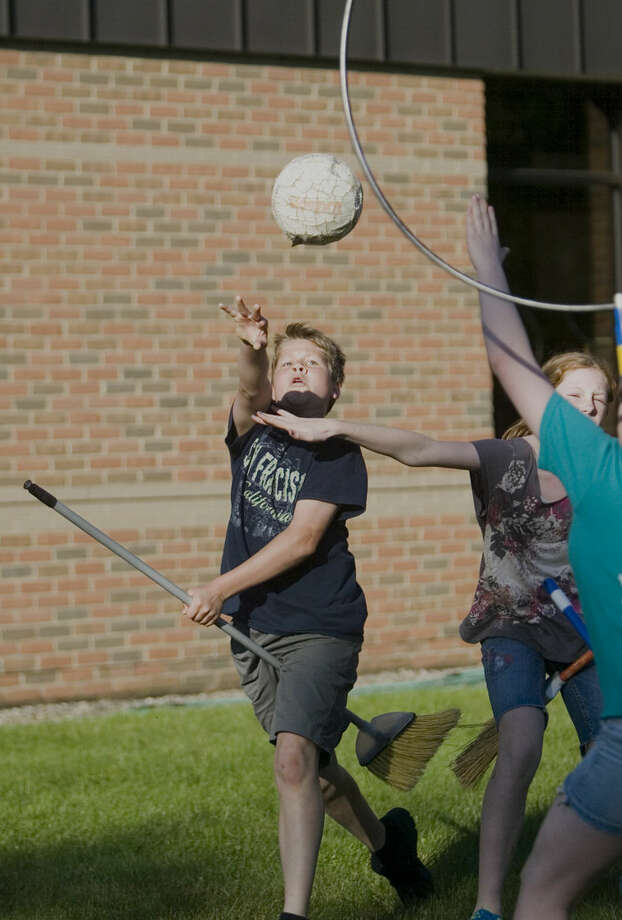 Konrad Laugenschlager, 12, shoots and scores for his team in an educational game of Quidditch held at the Brighton District Library. Photo: Gillis Benedict | Livingston County Daily Press & Argus Via AP
