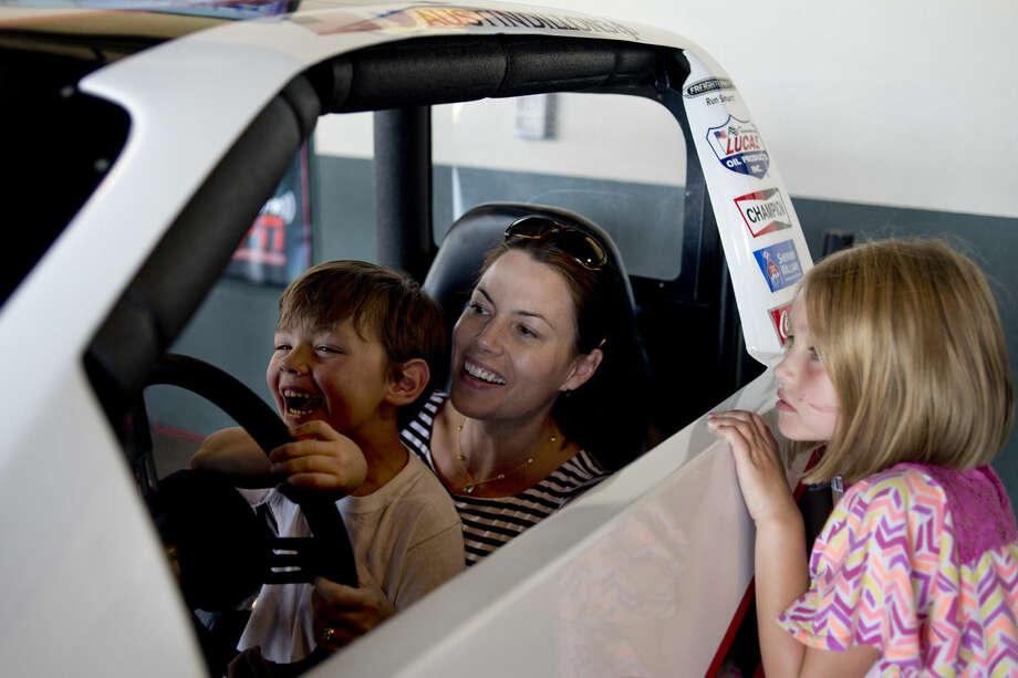 Oliver Parenteau, 5, sits on his mother Emily Parenteau's lap while driving in a race car simulator as Claire Parenteau, 7, all of Midland, watches at Dow Diamond Wednesday afternoon. NASCAR driver Austin Dillon and his pit crew visited Dow Diamond to sign autographs and display his No. 3 Dow Chevy show car. Photo: Brittney Lohmiller | Midland Daily News