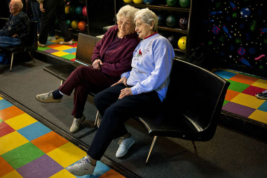 Marie Berlin, right, 89, talks with her sister Edith Woods, left, 92, between turns during their bowling league game a week ago Monday at Northern Lanes in Midland. The two sisters, who have been bowling together since the 1960s, get a ride to the alley from their nephew Tom Schaefer. Photo: Nick King/Midland  Daily News