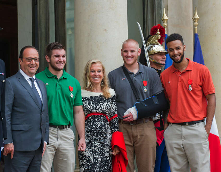 From left: French President, Francois Hollande, U.S. National Guardsman from Roseburg, Oregon, Alek Skarlatos, U.S. Ambassador to France Jane D. Hartley, U.S. Airman Spencer Stone and Anthony Sadler, a senior at Sacramento University in California, pose for photographers as they leave the Elysee Palace in Paris, France, after being awarded with the French Legion of Honor by French President, Francois Hollande, Monday, Aug. 24. French President Francois Hollande and a bevy of officials are presenting the Americans with the prestigious Legion of Honor on Monday. The three American travelers say they relied on gut instinct and a close bond forged over years of friendship as they took down a heavily armed man on a passenger train speeding through Belgium. Photo: Kamil Zihnioglu | AP Photo