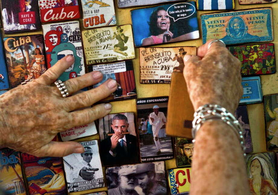 """An artesan named """"Buby"""" shows refrigerator magnets with images of U.S. president Barack Obama. Photo: Ramon Espinosa, AP"""