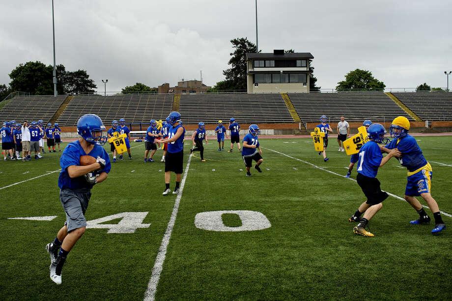 The Midland High School football team runs drills during practice on Monday at Midland Community Stadium. Photo: Nick King | Midland Daily News