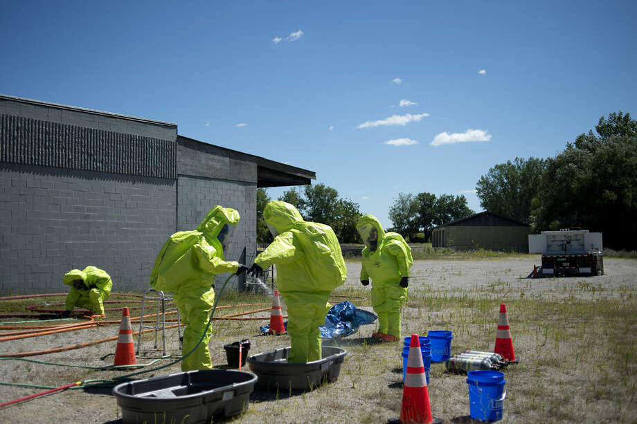 Members of the Midland Fire Department decontaminate their fully incapsulated HAZMAT suits after investigating a hazardous material leak during a training exercise on Thursday. Photo: Brittney Lohmiller | Blohmiller@mdn.net
