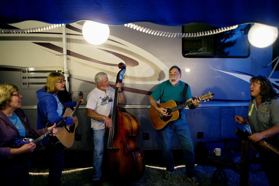 From left, members of the band Just Jammin' — Mickie Hedrich, playing the mandolin, Nancy Scigliano, playing the guitar, Larry Hedrich, playing the bass, Dave Scigliano, playing the guitar, and Pam Bowman, playing the hammer dulcimer — perform songs last year at the Midland County Fairgrounds during the Midland Folk Music Festival. Photo: Nick King | Midland Daily News File Photo