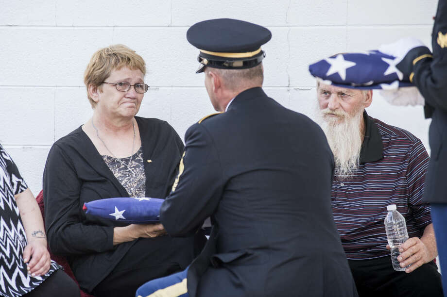 Jean Snear, center, accepts the burial flag for her son, Pfc. Robert Jeffrey Snear, as her husband, Ron Snear, right, looks on during their son's burial ceremony in Coleman on Monday. Photo: Erin Kirkland | Ekirkland@mdn.net