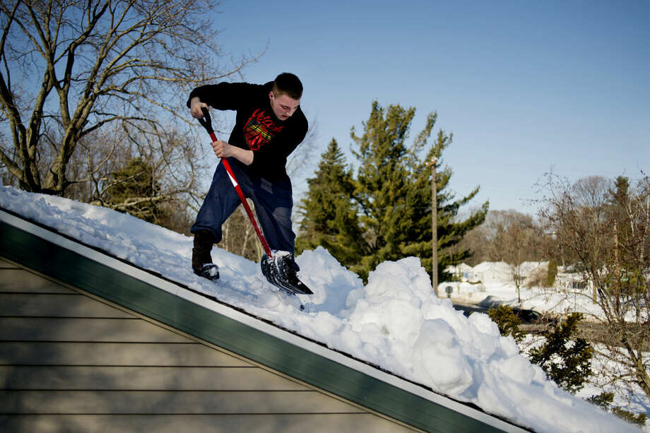 Joel Finney, 19, shovels off snow from his grandmother's home in Midland in February. Midland schools had to make up two days due severe weather. Photo: Neil Blake | Midland Daily News