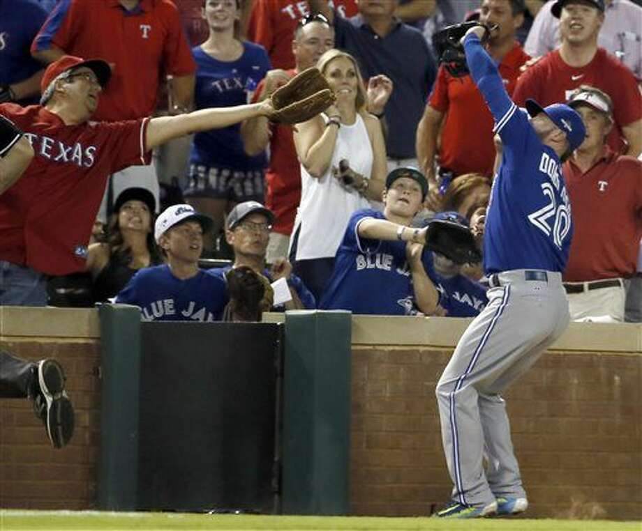 FILE - In this Sunday, Oct. 11, 2015 file photo, Toronto Blue Jays third baseman Josh Donaldson (20) grabs a fly-ball by Texas Rangers right fielder Shin-Soo Choo for an an out during the first inning in Game 3 of baseball's American League Division Series in Arlington, Texas. The Rangers have installed additional protective netting that spans the length of the dugouts on each side of their home ballpark. Rangers officials said Thursday, Feb. 18, 2016 that the new netting is about 6 feet high above the dugouts. That extends the nets from the end of the current home plate screen to over both dugouts, about 68 feet on both sides. (AP Photo/Tony Gutierrez, File) Photo: Tony Gutierrez