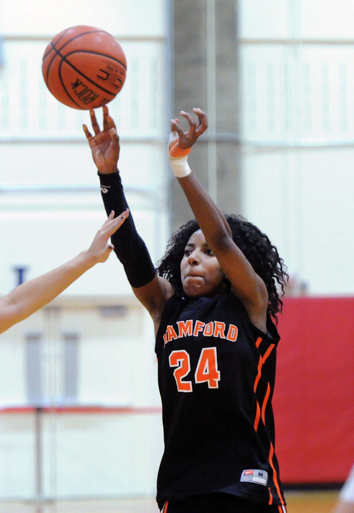 A hand in her face by a Greenwich defender does not stop Stamford's Tiana England (#24) from scoring on a jump-shot during the girls high school basketball game between Greenwich High School and Stamford High School at Greenwich, Conn., Wednesday, Feb. 3, 2016.