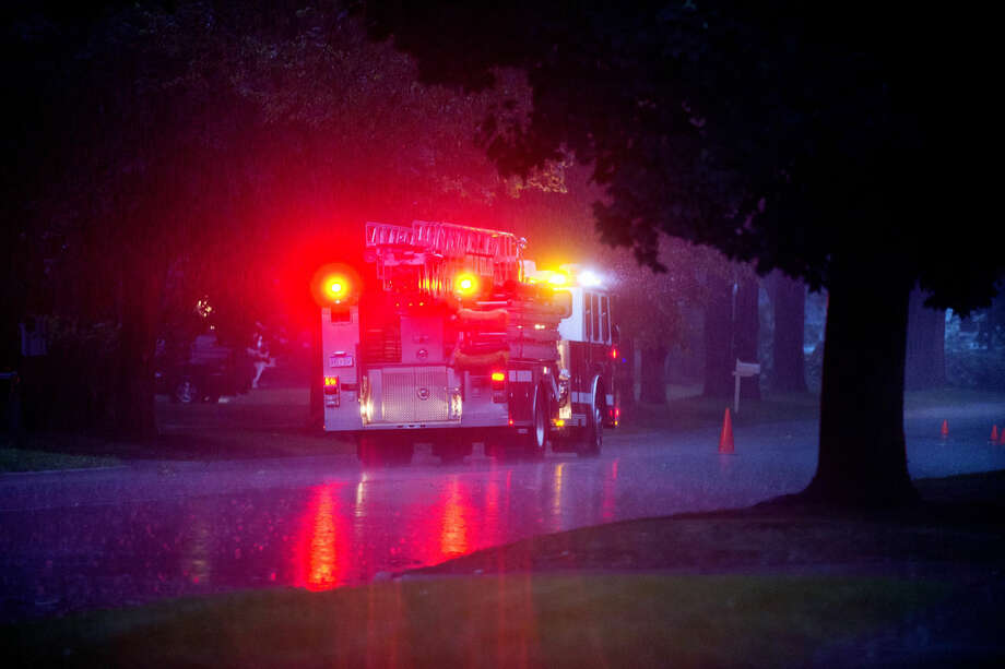 A Midland Fire Department truck sits outside a home near the site of a downed wire and toppled tree on East Ashman Street between Washington and Lindy streets on Sunday. Photo: Nick King | Nking@mdn.net