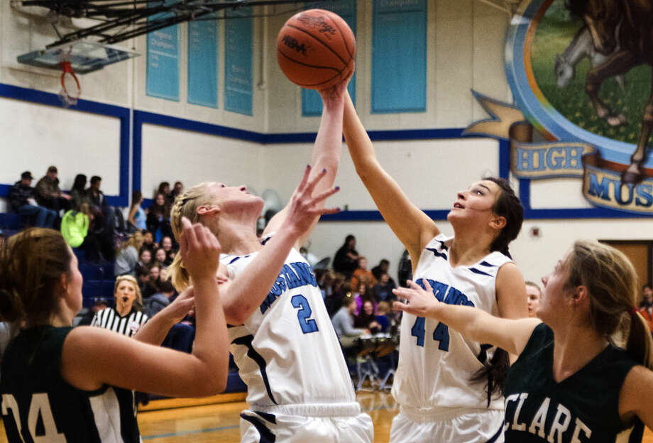 Meridian's Sarah Stockford (2) and Jillian Brady go up for a rebound as Clare's Morgan English, left, and Natalee Kunse watch at Meridian High School on Thursday. Photo: DANIELLE McGREW | For The Daily News