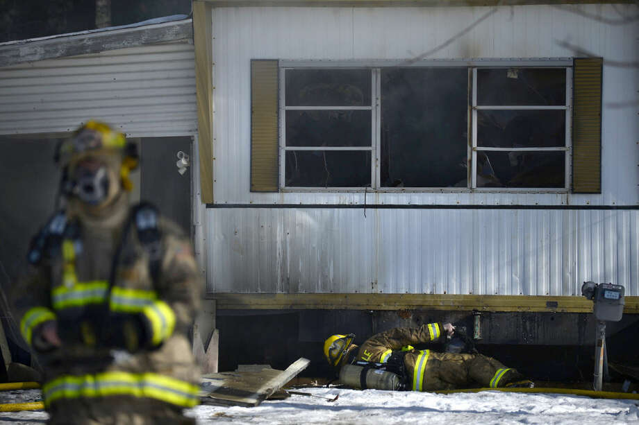Edenville Township firefighters work to put out a fire at 5582 North Lake Sanford Road Tuesday afternoon. Photo: BRITTNEY LOHMILLER | Blohmiller@mdn.net
