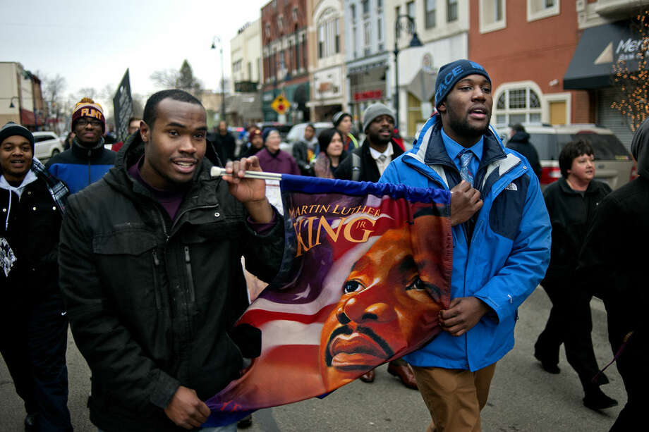Central Michigan University Senior Joshua Taylor, left, and freshman Devante Schofield carry a banner with the image of Martin Luther King Jr. while marching with a crowd down Main Street in Mount Pleasant during the Martin Luther King Jr. Peace March and Vigil on Monday. Photo: NICK KING | Nking@mdn.net