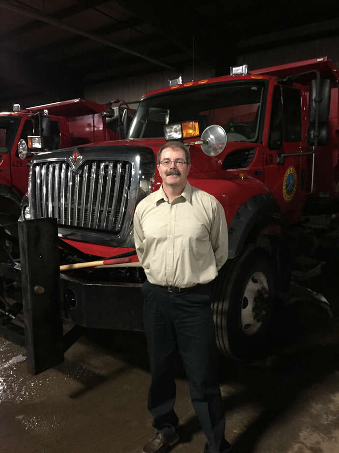 New Midland County Road Commission Director Terry Palmer stands in front of snowplows the county uses to clear roads. Photo: Photo Provided