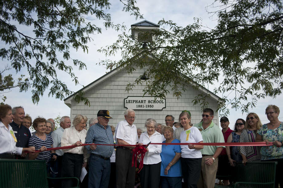 George Bartos, left, and his sister, Virginia Bartos, cut the ribbon for Leiphart School dedication Wednesday morning at the Midland County Fairgrounds. Both attended the school from 1931 to 1940. The school is at least 133 years old and was once located on Jefferson Avenue, then known as Old State Road. Photo: Brittney Lohmiller | Blohmiller@mdn.net