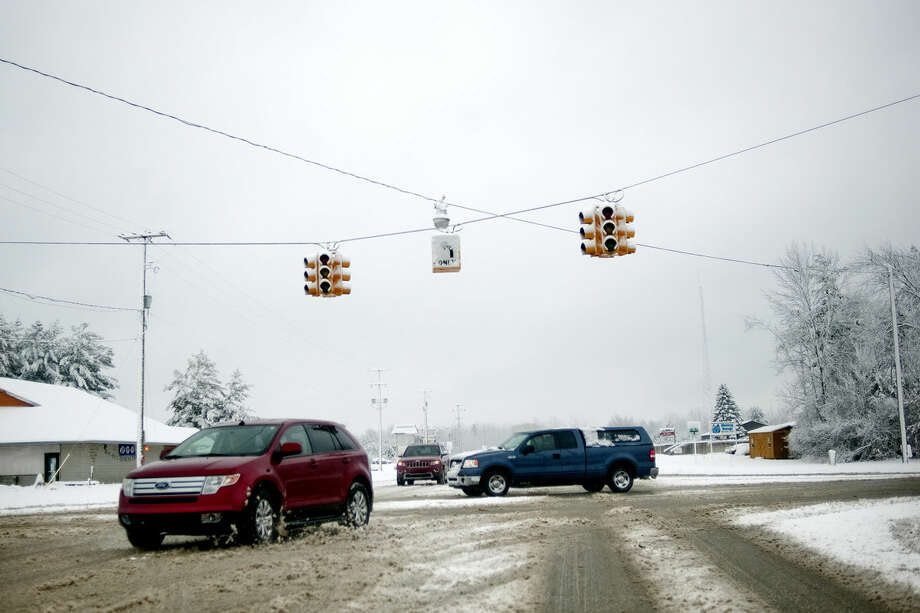 Vehicles move slowly through the intersection of Saginaw and Meridian roads in Sanford on Sunday after a snow storm knocked out power to the traffic lights. Photo: NICK KING | Nking@mdn.net