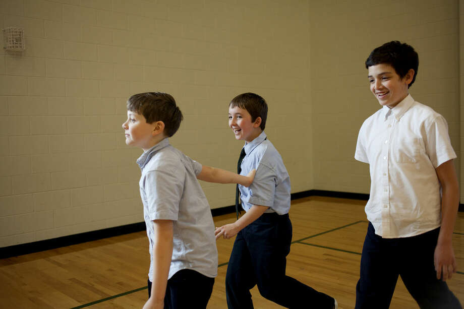 St. Brigid Catholic School student Lincoln Danner, left, pulls Michael Wilkowski as they walk with Dominic Rocha around the gym during a walk-a-thon to support Doctors Without Borders on Friday at the school. Photo: NEIL BLAKE | Nblake@mdn.net