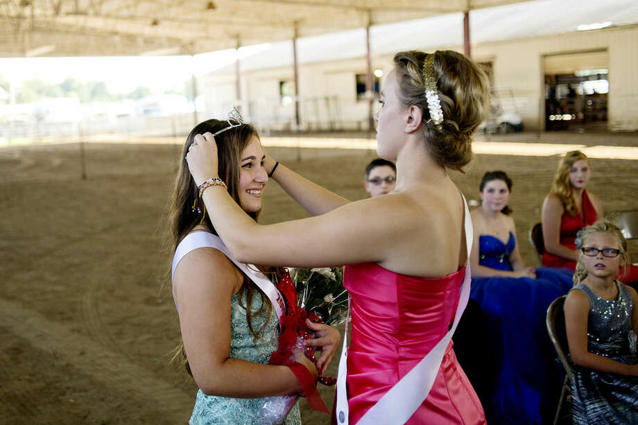 2014 Queen Ashleigh Reynolds, right, crowns Kalli Walz as the 2015 fair queen during the royalty contest on Saturday in the Glover Arena at the Midland County Fair. Photo: Nick King | Midland Daily News