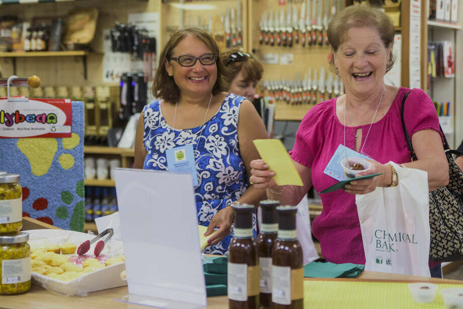 Debbie Hepinshall and Kathy Krotzer, both of Midland, were part of the Taste of Downtown event in Midland on Thursday. Photo: Danielle McGrew | For The Daily News