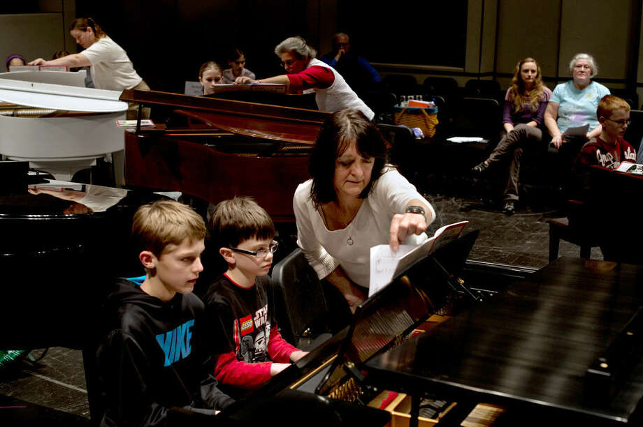 Mary Ann Anschutz of Midland turns a page as Thomas Metcalf, 8, center, and Jack Miller, 10, practice their four-handed duet during a recital practice for KeyboardFest at the Midland Center for the Arts. Anschutz has taught piano for 40 years and been involved with KeyboardFest since the first recital. Now the local music educator and supporter also has been named as the Midland Center for the Arts Musician of the Year. Photo: SEAN PROCTOR | Sproctor@mdn.net