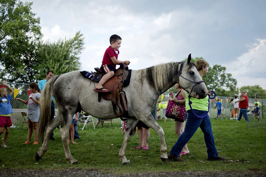 Shane Jones, 6, rides a horse led by Gale Kissinger, right, during the West Midland Family Center 40th anniversary celebration in July. Photo: NICK KING | Nking@mdn.net