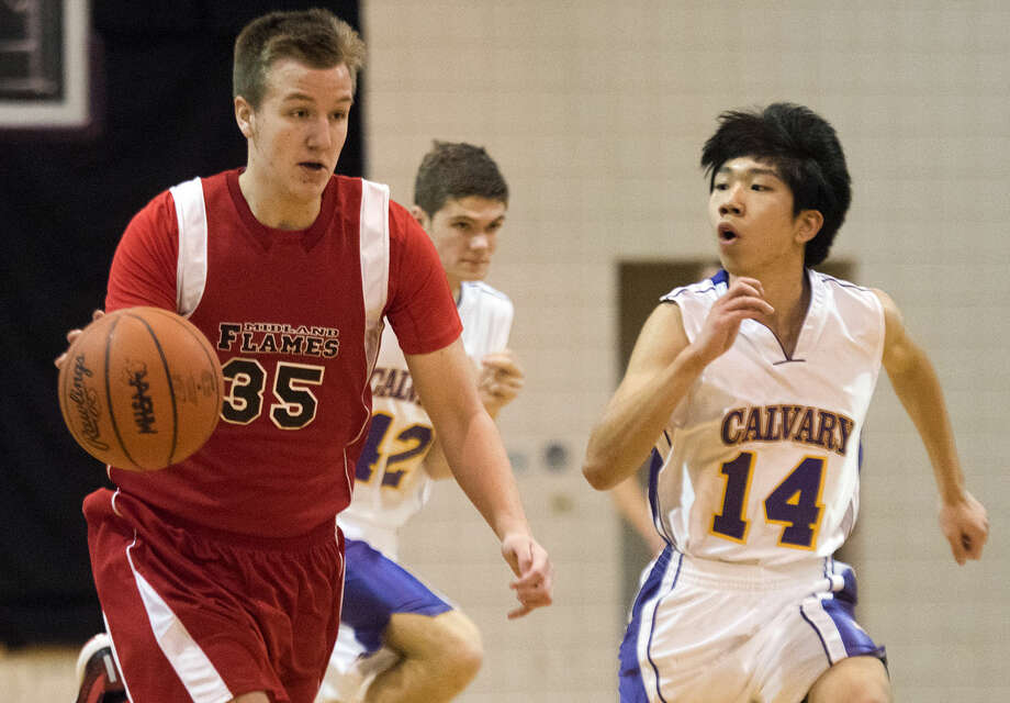 The Flames' Nate Winterstein dribbles down the court, pursued by Calvary's Justin Kim at Calvary Baptist Academy in Midland on Tuesday. Photo: DANIELLE McGREW | For The Daily News