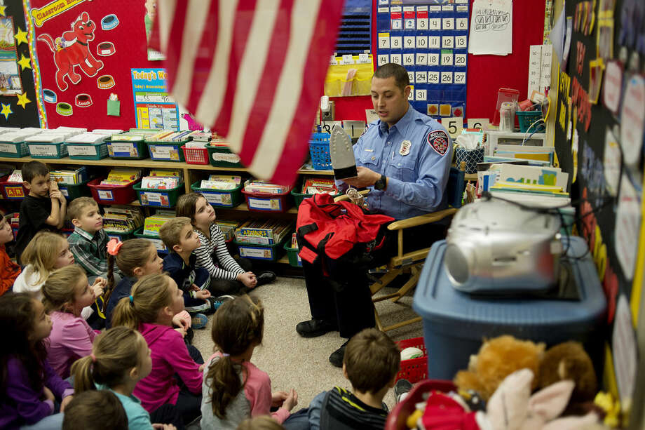 Midland firefighter Mark Laux talks to Helen Gibbons' first grade class at Adams Elementary about the dangers of hot objects. Laux talked to the students about the importance of staying away from fire starters like matches and lighters. Photo: NEIL BLAKE | Nblake@mdn.net
