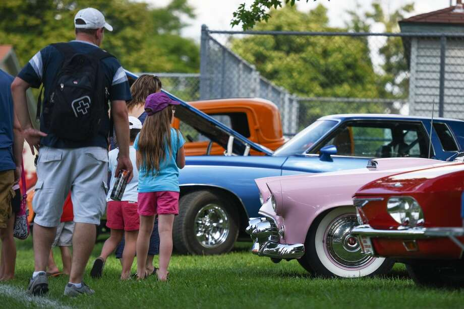People look at classic cars parked in Memorial Park during the Woodward Dream Cruise, Friday, Aug. 14, 2015, in Royal Oak, Mich. (Tanya Moutzalias/The Ann Arbor News-MLive.com Detroit via AP) LOCAL TELEVISION OUT; LOCAL INTERNET OUT; MANDATORY CREDIT Photo: Tanya Moutzalias