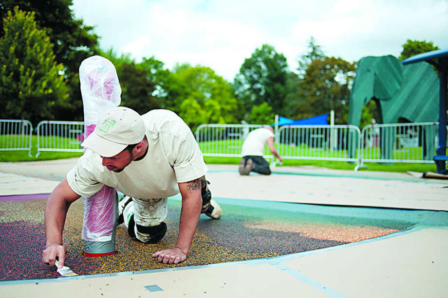 Justin Hardwick, left, and Jon Wilbanks with Equi-Turf paint on primer before spraying a seamless rubber surface to the splash pad at Thrune Park Tuesday afternoon. Photo: Brittney Lohmiller/Midland Daily News
