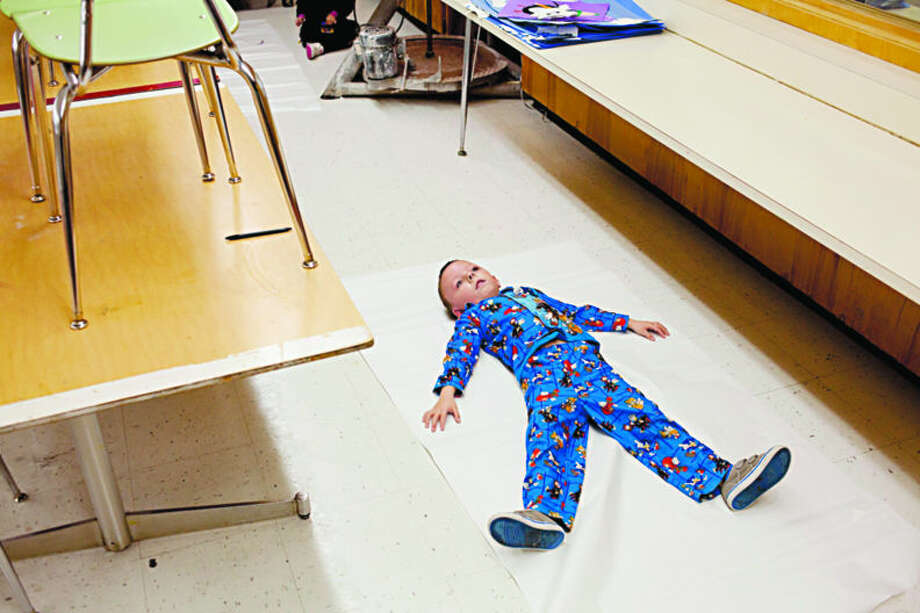 Carpenter Elementary School kindergartner Braden Powers holds still while waiting for Spanish teacher Yolanda Collier to trace around him on Friday. The students were studying body parts in class and coloring life-size tracings of themselves. Friday was a Spirit Day at the school, and students and teachers dressed in their pajamas. Photo: Neil Blake/Midland Daily News