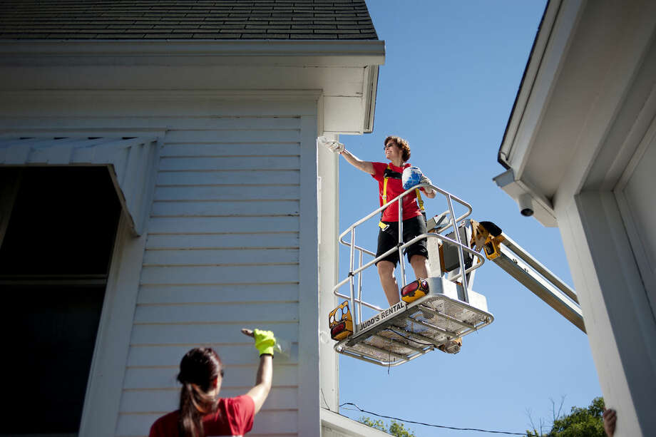 """Chandler Berthiaume, of Bay City, left, and Rhonda Henning, of Sanford, give a house at 508 Rodd St. a fresh coat of paint during the Habitat for Humanity Neighborhood Revitalization Project. """"I love helping people,"""" Henning said. """"People have helped me before so I like to pay it forward."""" Photo: Brittney Lohmiller 