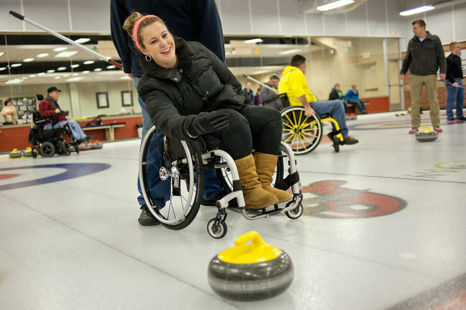 Brittany Maxwell smiles after releasing a curling stone as she and others participate in a wheelchair curling clinic on Saturday at the Midland Curling Club. Photo: NICK KING | Nking@mdn.net