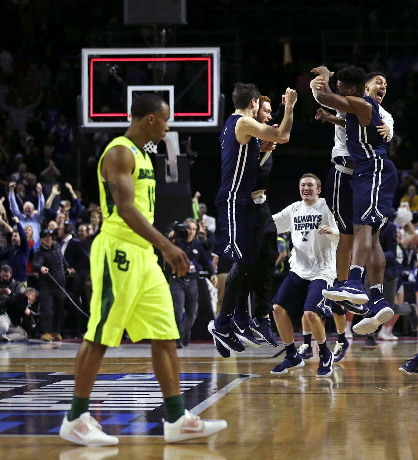 Yale celebrates their victory as Baylor guard Lester Medford (11) walks off the court during the first round of the NCAA college men's basketball tournament in Providence, R.I., Thursday, March 17, 2016. Yale defeated Baylor 79-75. (AP Photo/Charles Krupa) Photo: Charles Krupa, AP