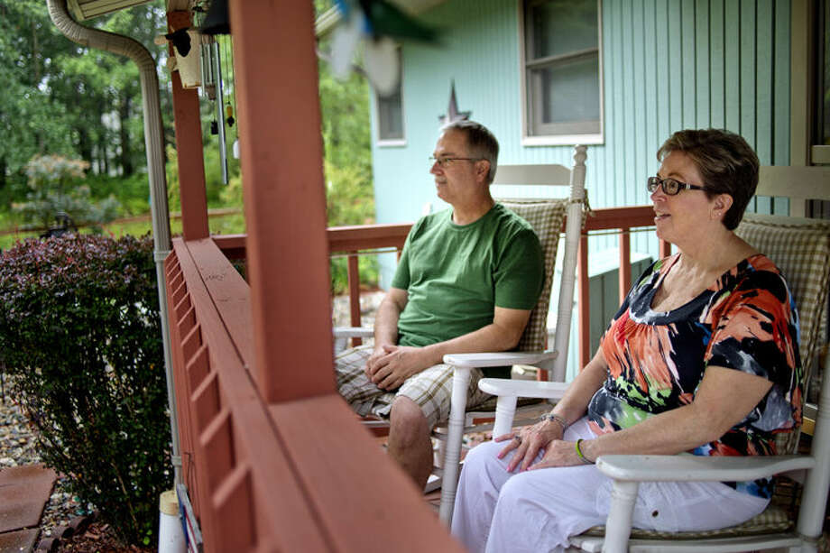 NICK KING | nking@mdn.net Tammie Church, right, and her husband Kevin enjoy their time out on the front porch of their home on Monday in Midland. The Churches' set up a GoFundMe site to help raise money to make their bathroom accessible for Tammie who has Parkinson's disease. Photo: Nick King/Midland Daily News