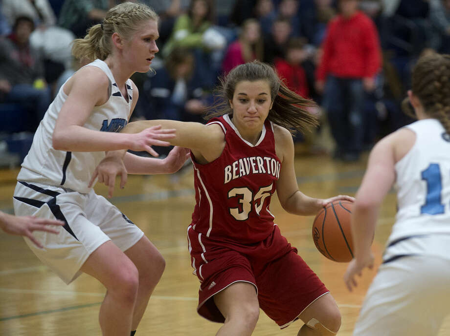 Breanna Frasher of Beaverton dribbles past Sarah Stockford, left, and Caitlin Drouin of Meridian in the second half the game Thursday evening at Meridian High School. Beaverton defeated Meridian 65-51. Photo: BRITTNEY LOHMILLER | Blohmiller@mdn.net