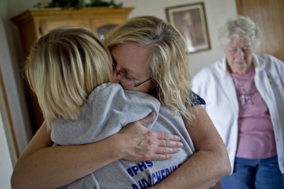 "ERIN KIRKLAND | ekirkland@mdn.net Barb Aultman hugs daughter Nicole Aultman, 18, in their Mt. Pleasant home on Tuesday after helping sister Chelsea Aultman, 18, pack up to move to Davenport University in Grand Rapids where she will study business. Nicole will also be moving to Grand Rapids to study physical therapy at Grand Valley State University. Brother Riley Aultman, 18, will not leave Mt. Pleasant until December when he will ship off to Marine bootcamp at Fort Benning in San Diego, CA. All three siblings were born prematurely as quadruplets in 1997. Sister Kayla Aultman died at 18 months due to complications from her premature birth.""This last year has been really tough,"" mother Barb Aultman said. ""I keep wondering where she would be going and what she would be doing."" Photo: Erin Kirkland/Midland Daily News"