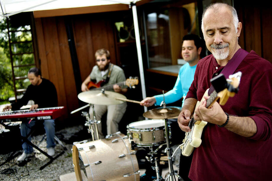FILE — Bryan Rombalski, right, along with Three Worlds band members, from left, John Talbert, Ryan Fitzgerald and Eddy Garcia, perform for guests during Dahlia Hill's Autumn Equinox Celebration. (Daily News File) Photo: Nick King | Midland Daily News