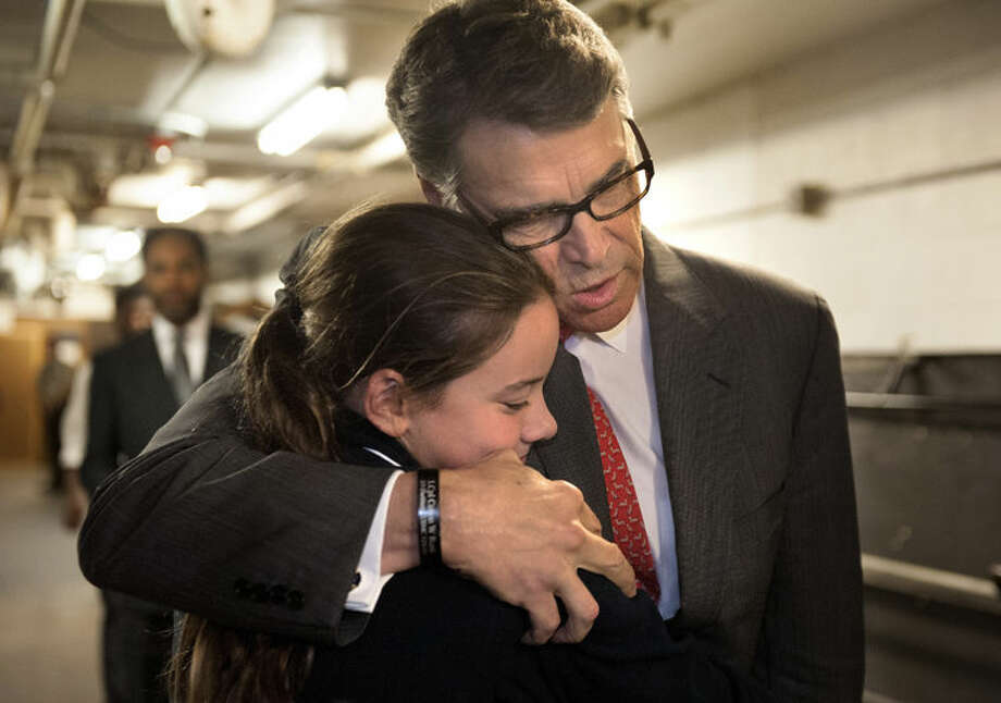 Republican presidential candidate, former Texas Gov. Rick Perry embraces Madeline Martin, daughter of Eagle Forum president Ed Martin, before speaking at the Eagle Council XLIV in St. Louis Friday. During the speech Perry said he is ending his second bid for the Republican presidential nomination, becoming the first major candidate of the 2016 campaign to give up on the White House. Photo: Sid Hastings | AP Photo