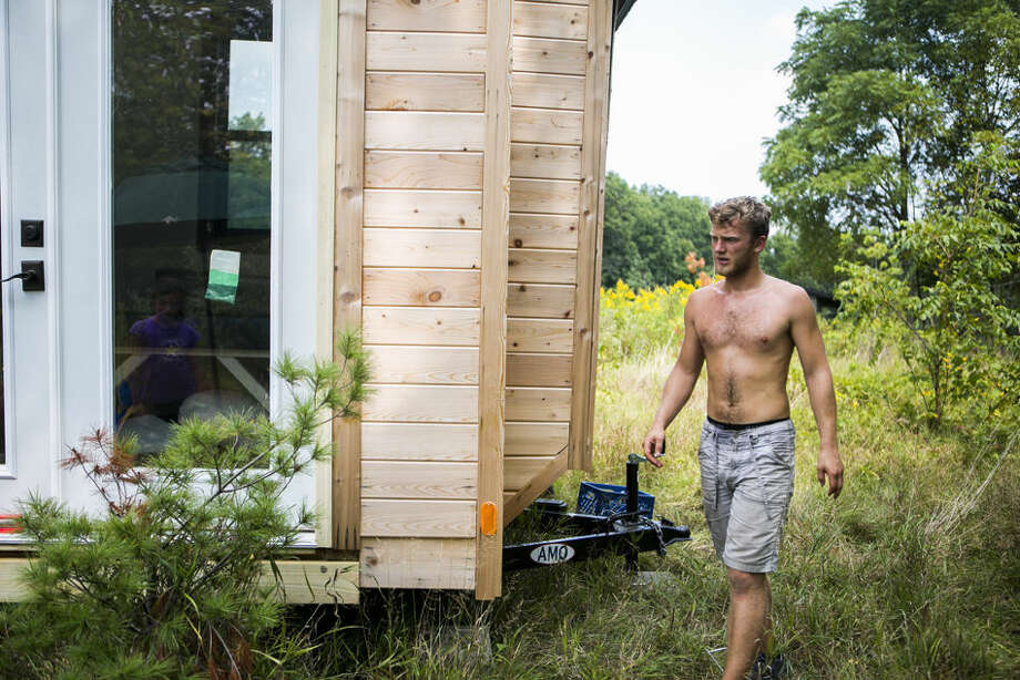 "In this Wednesday, Sept. 2, 2015 photo, Christopher Cerk installs his tiny house, which he built by hand, in Ann Arbor, Mich. Cerk, 21, says, ""Around freshman year I didn't enjoy living in the dorms so I wanted to do something different. I started researching different ways to live. I wanted to put all the money that would be going towards rent ... to something else."" Photo: Dominic Valente/The Ann Arbor News Via AP"