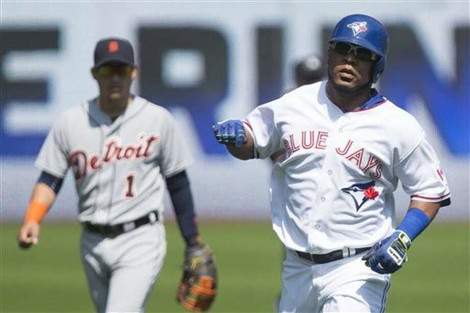 Toronto Blue Jays' Edwin Encarnacion, right, rounds the bases after hitting a solo home run off Detroit Tigers starting pitcher Alfredo Simon as Tigers' shortstop Jose Iglesias, left, looks on during first-inning baseball game action in Toronto, Sunday, Aug. 30, 2015. (Chris Young/The Canadian Press via AP) MANDATORY CREDIT Photo: Chris Young