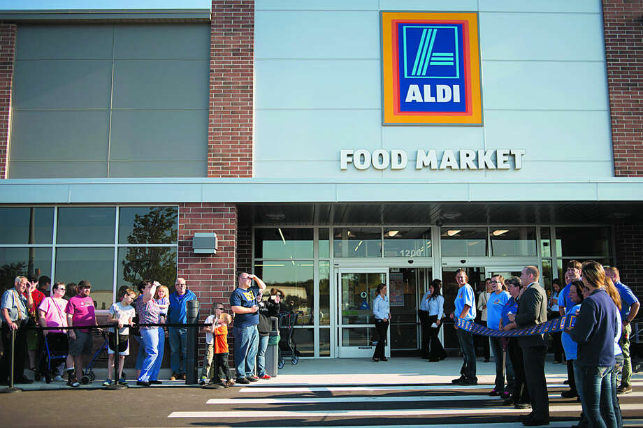 ALDI grocery store manager June Short cuts the ribbon during the grand opening of the store Thursday morning. The new store is 20,100 square feet and is located where the Best Buy store was before it closed in February. Photo: Brittney Lohmiller | Midland Daily News