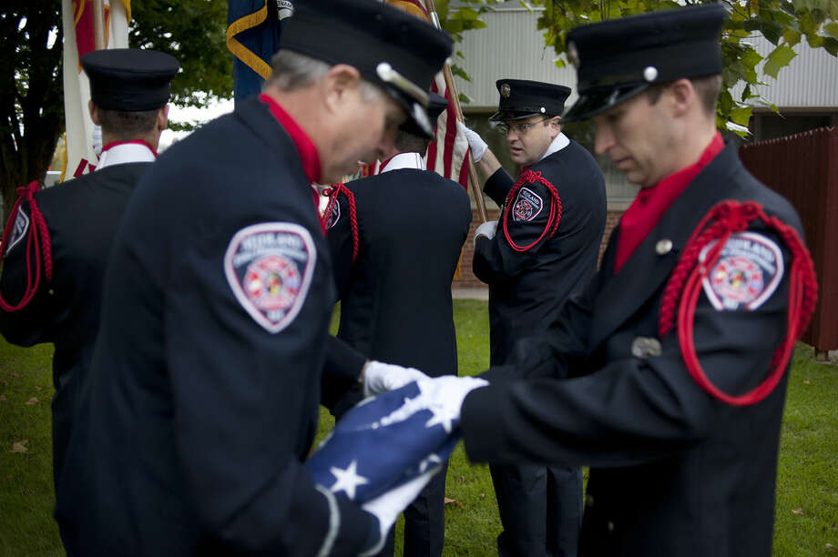 Midland Fire Department fire truck operator Chris Lince watches Lt. Greg Grobbel, left, and firefighter Phil Hepworth tuck in the edges of the American flag before raising it to half mast during a remembrance ceremony for the 2,996 lives lost on Sept. 11, 2001. These lives included 343 firefighters, 72 law enforcement officers and 55 military personnel. Photo: Brittney Lohmiller | Midland Daily News