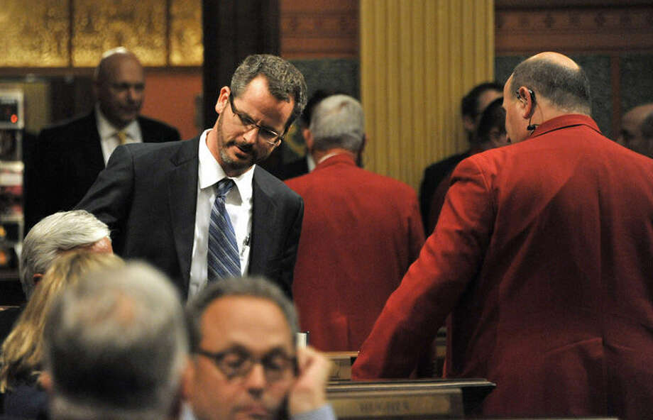 House sergeants escort state Rep. Todd Courser, standing left, from the chamber after he signed a letter of resignation in Lansing. The extramarital affair between Courser and Rep. Cindy Gamrat became public last month, ultimately leading to both Republicans losing their seats. Photo: Dale G. Young | Detroit News Via AP