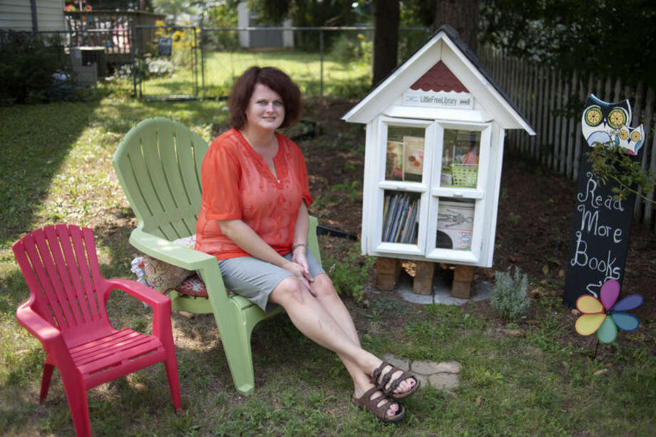 Sheila McCoy of Midland set up a lending library on her front lawn on West Carpenter Street. Neighbors, community members, adults and children, can borrow books for free. Photo: Brittney Lohmiller/Midland Daily News
